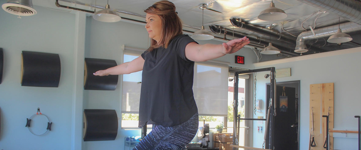woman balancing on a pilates reformer